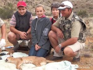 La famille Lund avec la femelle caracal Ginger lors de sa capture. Impliquer les fermiers – et notamment les enfants – lors des captures est une excellente façon de parler de la biologie des prédateurs et de les leur montrer vivants plutôt que morts.